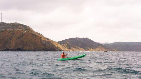 Man paddles a kayak over the sea of Montanita beach in Ecuador Stockfoto - 134888592