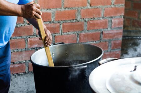 An Andean mans hand moving the wooden spoon in a pot, Andean rustic cuisine