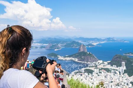 A woman with a camera taking picture of the landscape from Corcovado Mountain in Brazil