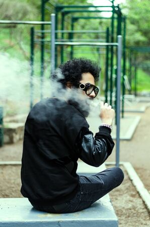 Man with a beard smokes an electronic cigarette sit on a bench in the park