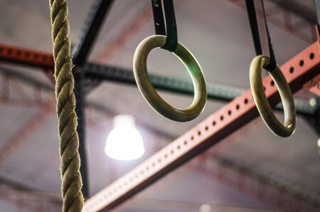Gymnastic rings in crossfit gym, workout background interior. Motivation.