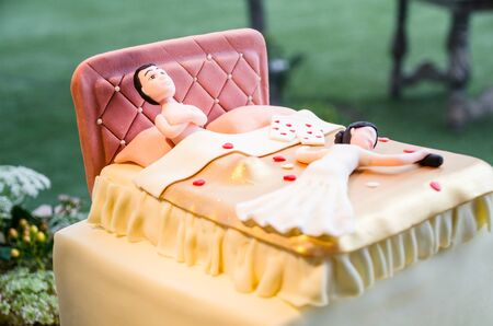 Wedding bride and groom couple doll in funny action at the wedding cake, boyfriends lying tired in bed