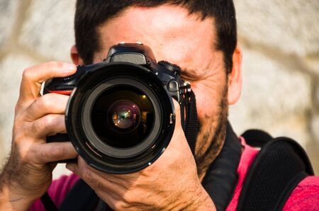 Photographer, taking photos with his professional camera with both hands