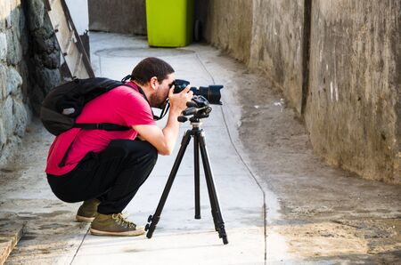 Crouched professional photographer taking photos on a sunny day in the city Stok Fotoğraf