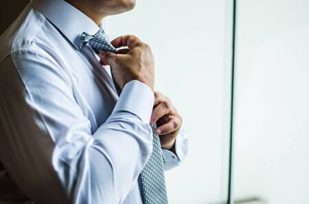 Businessman making a tie knot, formal suit