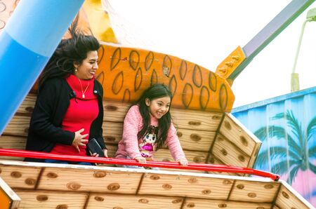 Mom and daughter having fun and smiling in an amusement park game