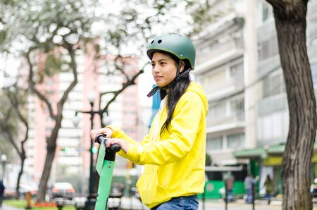 Cheerful woman with yellow shirt riding an electric scooter. Stock Photo