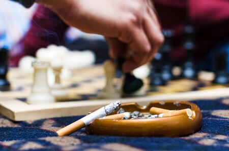 Cigar on an ashtray with the background of a game of chess