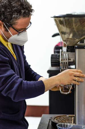 A barista grinding some coffee beans to make espresso