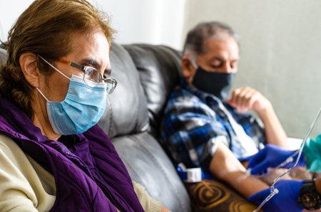 Elderly couple receiving vitamin C transfusion, prevention against covid