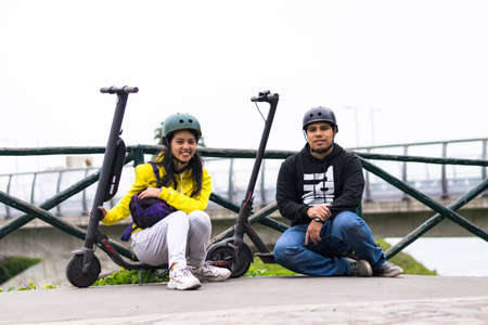 Two smiling friends showing helmet, concept in driving safety with a means of transportation Standard-Bild