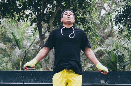 Portrait of a physically fit man posing with skipping rope
