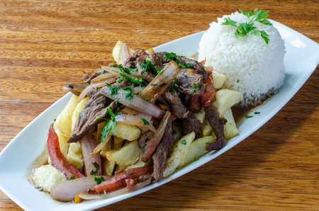 Peruvian dish called Lomo Saltado made of tomato, beef meat and onions mixed with French fries and served with rice Standard-Bild