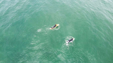 Two surfers sails on a surfboards in a calm ocean, top view