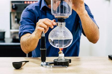 Professional coffee maker - Barista using coffee siphon brewing hot espresso at coffee shop Standard-Bild