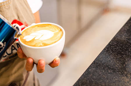 Hands of a Peruvian barista creates latte art in coffee shop, food and drink concept