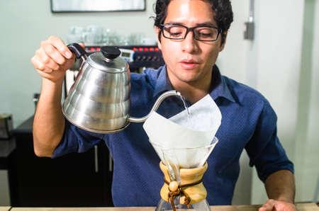 Portrait of professional barista making coffee