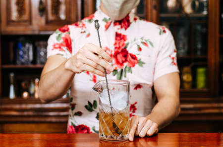 Barman pouring whiskey wearing protective mask on the bar counter Standard-Bild