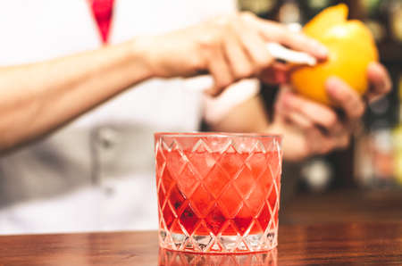Close up shot of bartender hands preparing negroni cocktail with grapefruit. He is putting some essence from grapefruit skin into the cocktail glass on counter Standard-Bild