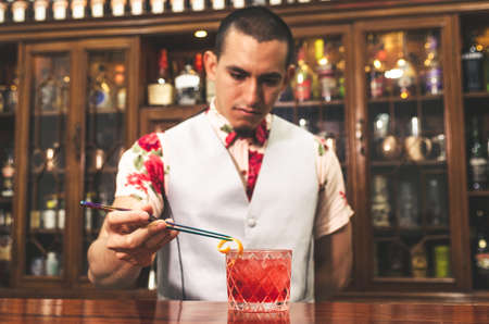Bartender preparing negroni cocktail with grapefruit. He is putting some essence from grapefruit skin into the cocktail glass on counter Standard-Bild