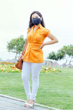 Woman in city street wearing mask protective for spreading of disease virus SARS-CoV-2