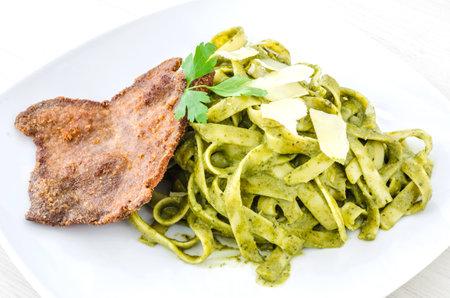 Tallarin Verde con Bistec is a famous Peruvian dish. It is Pesto spaghetti with crumbed steak.