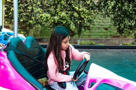 Boy driving a bumper car. Motion blur image.