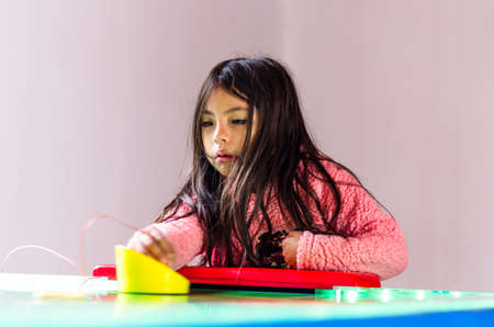 Concentrated and enthusiastic girl plays table hockey. Standard-Bild