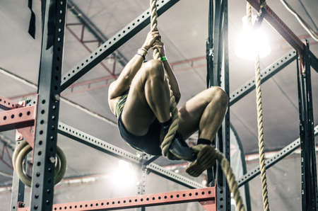 Unrecognizable young athletic woman working and climbing a rope in a gym. Standard-Bild