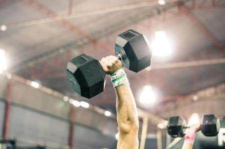 The hand of a muscular man lifting a dumbbell in the gym.