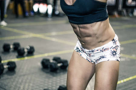 Torso of a young woman in the form of weightlifting with the background of a gym.