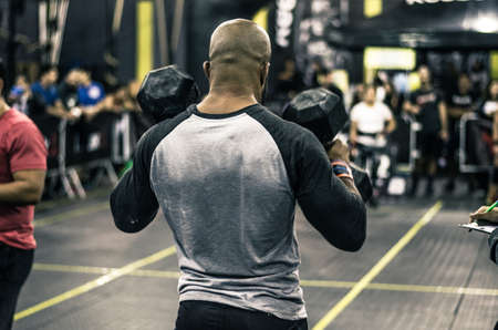 Sport. Muscular african man lifting weights in a gym