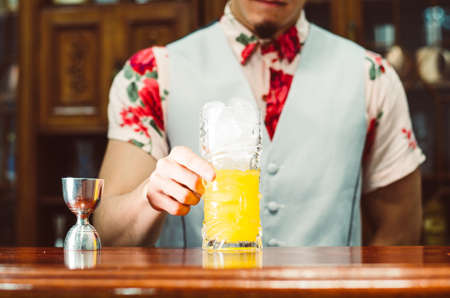 Bartender showing cocktail in a tiki glass on a bar counter on a blurred background of bottles in a bar. Standard-Bild