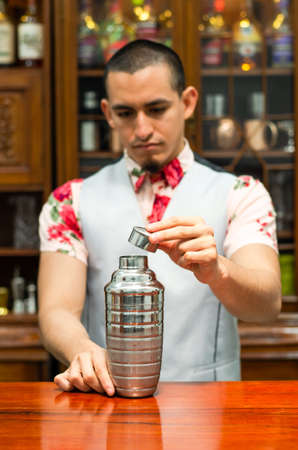 Young handsome smiling barman in bar interior shaking and mixing alcohol cocktail.