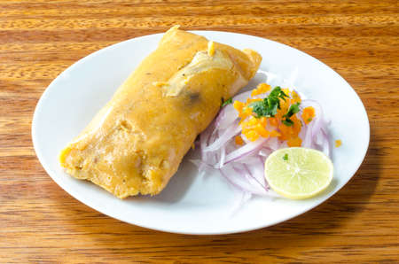 Peruvian tamale, traditionally eaten for breakfast on Sundays, made of corn and chicken and served with salsa criolla - onion salad.