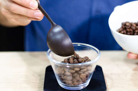 Weighing coffee grains on digital scale. Hands of male barista pouring roasted coffee grains on a scale before brewing coffee.