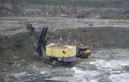 Quarry. Loading by the bulldozer of truck of stones photo