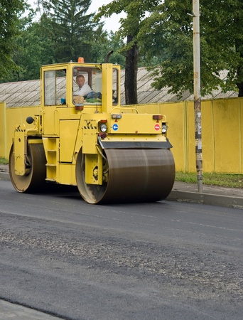 asphalt spreader is used to place the first layer of asphalt on a city street renewal project photo