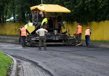 road paving: asphalt spreader is used to place the first layer of asphalt on a city street renewal project
