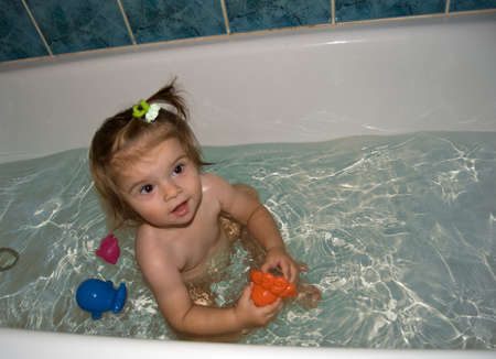 Child in bath with toys photo