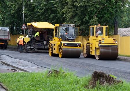 steamroller: asphalt spreader is used to place the first layer of asphalt on a city street renewal project