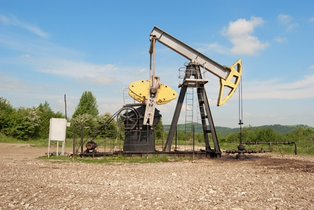 Oil and gas industry. Work of oil pump jack on a oil field. White clouds and blue sky  Stock Photo - 14176879