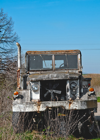 a military truck is neglected in field photo