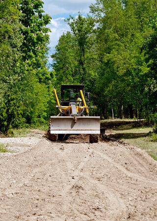resurfacing: large yellow grader resurfacing a narrow rural road