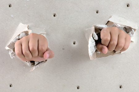 broken through: a wall is broken through by a two fist Stock Photo