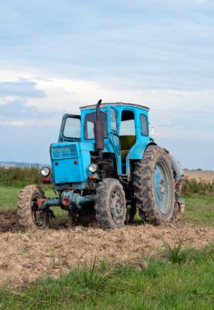 old tractor: blue old tractor in autumn on field