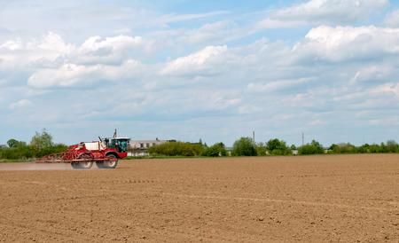 mechanization: agricultural fertilizer spreader spraying dry fertilizer on farm fields Stock Photo