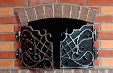 Close up of brick fireplace with an iron gate photo