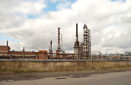 petrol bomb: old refinery releasing on the blue sky