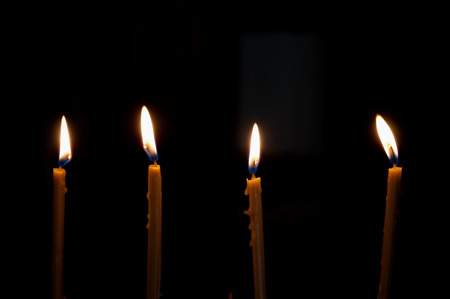 alight: four alight candles over the black background Stock Photo